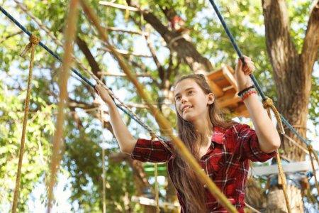 Teenage girl climbing in adventure park. Summer ca...