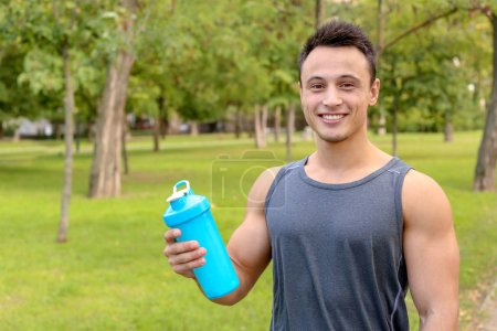 Man with bottle of protein shake in park. Space fo...