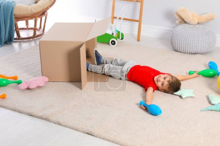 Cute little boy playing with cardboard box at home