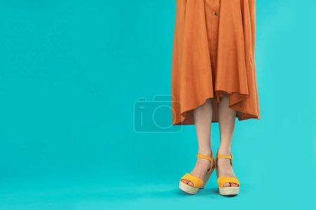 Woman in stylish shoes on light blue background. S...