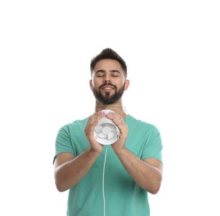 Photo pour Man enjoying air flow from portable fan on white background. Summer heat - image libre de droit