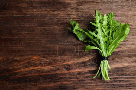 Photo for Fresh arugula on wooden table, top view. Space for text - Royalty Free Image