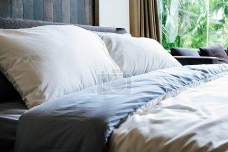Photo pour Lit blanc moderne et oreiller dans l'humeur du matin - image libre de droit