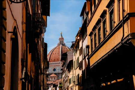 FLORENCE, ITALY - JULY 17, 2017: narrow street and famous Basilica di Santa Maria del Fiore in Florence, Italy