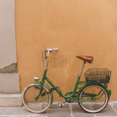 Photo for Vintage green bicycle standing near orange wall, Pisa, Italy - Royalty Free Image