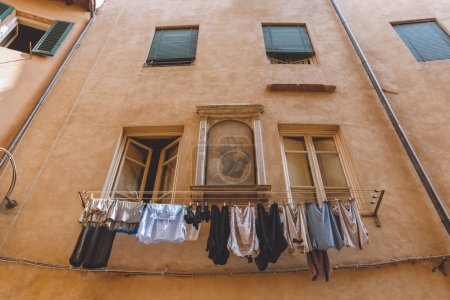 Photo for Laundry hanging outside buildings with icon on wall in Pisa, Italy - Royalty Free Image