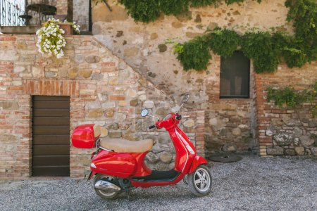 Photo for TUSCANY, ITALY - AUG 27, 2017: urban scene with red motorbike parked on street and architecture of Tuscany, Italy - Royalty Free Image