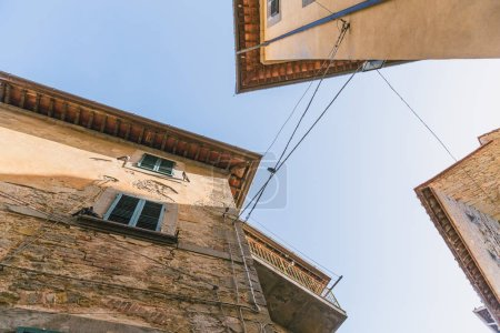 bottom view of buildings and clear blue sky in Tuscany, Italy