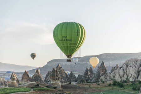 CAPPADOCIA, TURKEY - 09 MAY, 2018: hot air balloons flying above beautiful rock formations in goreme national park, cappadocia, turkey