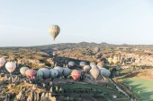 CAPPADOCIA, TURKEY - 09 MAY, 2018: hot air balloons flying above beautiful landscape in goreme national park, cappadocia, turkey