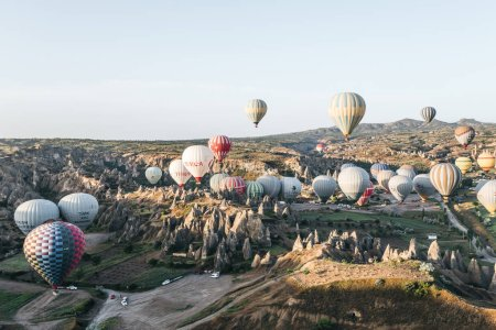 Photo for CAPPADOCIA, TURKEY - 09 MAY, 2018: hot air balloons flying above beautiful bizarre rock formations in goreme national park, cappadocia, turkey - Royalty Free Image
