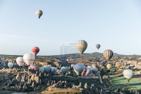 Photo pour Cappadoce, Turquie - 9 mai 2018: belles montgolfières volant au-dessus d'étranges formations rocheuses en Cappadoce, Turquie - image libre de droit