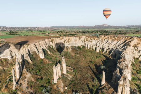 single hot air balloon flying above beautiful famous rock formations in cappadocia, turkey