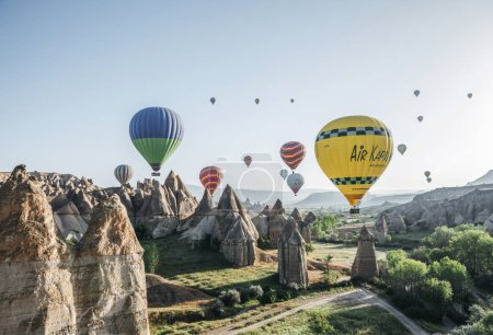 Photo for CAPPADOCIA, TURKEY - 09 MAY, 2018: colorful hot air balloons flying in sky above majestic rock formations in famous cappadocia, turkey - Royalty Free Image