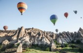 CAPPADOCIA, TURKEY - 09 MAY, 2018: colorful hot air balloons flying in sky above beautiful rock formations in cappadocia, turkey