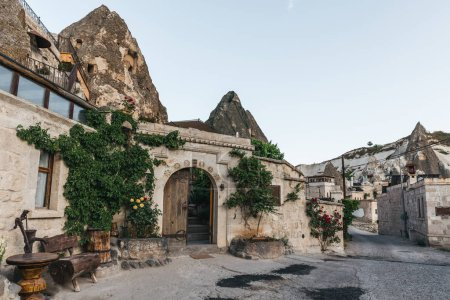traditional buildings with green plants and beautiful rock formations in cappadocia, turkey