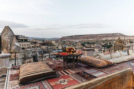 Foto de Mesa redonda, almohadas tradicionales y alfombra turca en terraza y hermosa vista de la arquitectura tradicional y las rocas de Capadocia, Turquía - Imagen libre de derechos