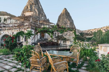 Photo for Table and chairs on terrace and majestic view at bizarre rock formations in cappadocia, turkey - Royalty Free Image