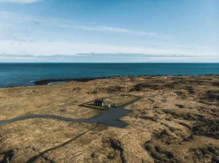 aerial view of small black Budir Church near beautiful sea, snaefellsnes, iceland