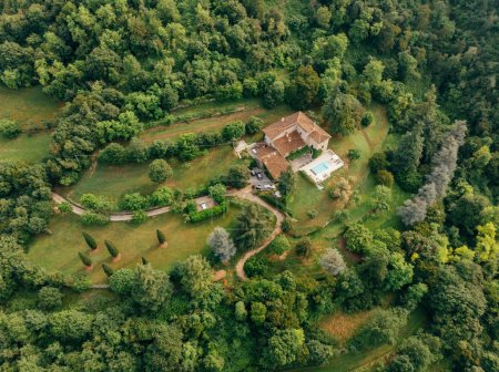 aerial view of villa with swimming pool between forest in Italy