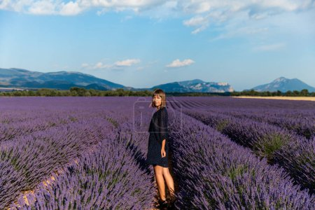 beautiful young woman standing on lavender field and looking at camera, provence, france
