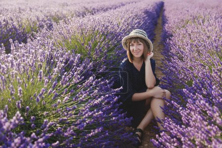 Photo for Beautiful young woman sitting between blooming lavender flowers and smiling at camera, provence, france - Royalty Free Image