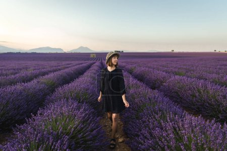 Photo for Beautiful young woman standing between blooming lavender flowers and looking away, provence, france - Royalty Free Image