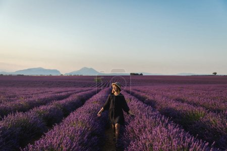 Photo for Beautiful young woman walking between blooming lavender flowers, provence, france - Royalty Free Image