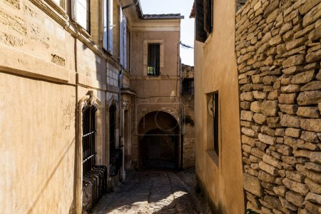 cozy narrow street with old stone buildings in provence, france