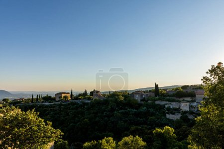 Photo for Tranquil landscape with cozy traditional houses, green vegetation and distant mountains in provence, france - Royalty Free Image