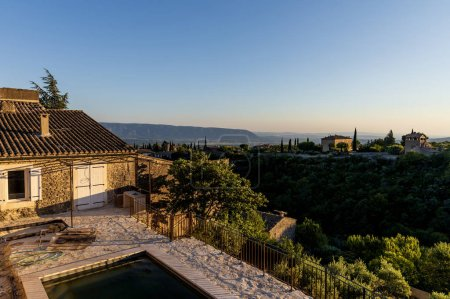 beautiful tranquil landscape with cozy traditional houses and distant mountains in provence, france