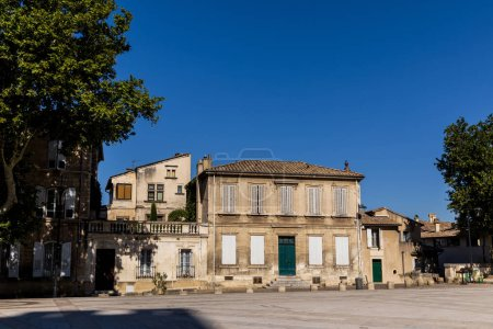 empty street with old traditional houses and green trees at sunny day, provence, france
