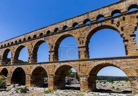 Photo for Pont du Gard (bridge across Gard) ancient Roman aqueduct across Gardon River at sunny day in  Provence, France - Royalty Free Image