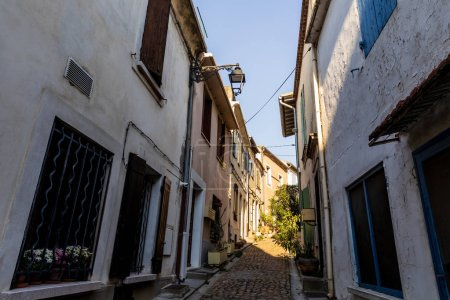 Photo for Low angle view of cozy narrow street with traditional white houses in provence, france - Royalty Free Image