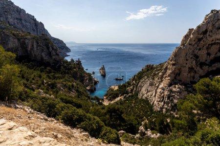 Foto de Montañas rocosas con vegetación verde y barcos en Puerto, Calanques de Marseille (macizo des Calanques), Provenza, Francia - Imagen libre de derechos