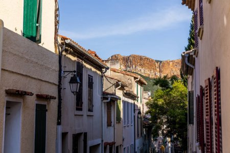 Photo for Cozy narrow street with traditional houses and distant rocky mountains in provence, france - Royalty Free Image