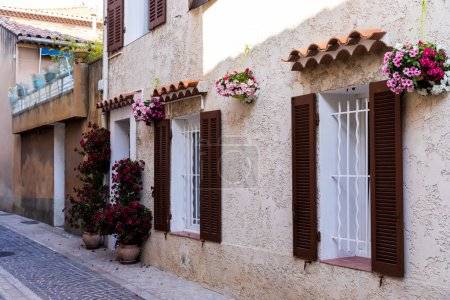 Photo for Cozy narrow street with traditional houses, flower pots and shutters in provence, france - Royalty Free Image