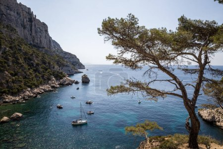Foto de CALANQUES DE MARSEILLE, FRANCE - JUNE 18, 2018: boats in calm harbour and beautiful rocky mountains in Calanques de Marseille (Massif des Calanques) - Imagen libre de derechos