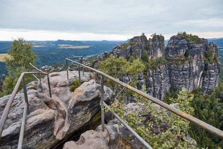 Photo pour Garde-corps sur beaux vieux rochers et forêt sur fond Bastei, Allemagne - image libre de droit