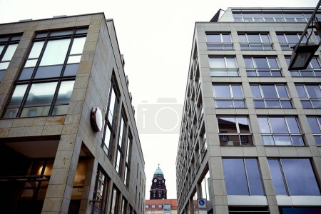 low angle view of old historical tower with clock between modern buildings in Dresden, Germany