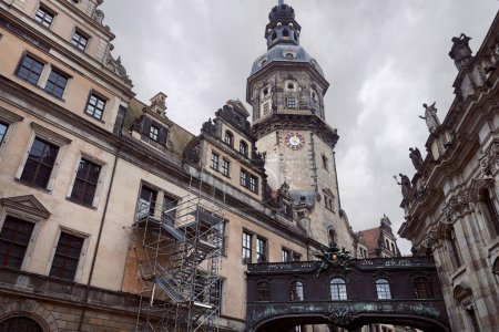 Low angle view of old dresden cathedral with clock, statues on building roof in Dresden, Germany