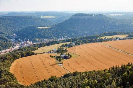 Foto de Vista aérea de campos agrícolas con cosecha cerca de la aldea y las montañas en Bad Schandau, Alemania - Imagen libre de derechos