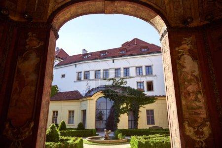 Foto de República Checa, Praga - 26 de junio de 2018: vista a través de arco en fuente y arbustos en el patio - Imagen libre de derechos