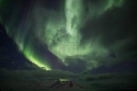 Photo pour Aurores boréales au-dessus du ciel nocturne nuageux - image libre de droit
