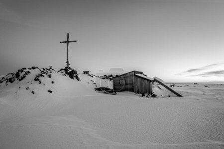 Photo for View of the cross and snow-covered wooden house - Royalty Free Image