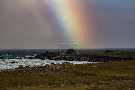 Photo pour Vue de la croix sur la côte rocheuse de l'océan nordique avec un arc-en-ciel - image libre de droit