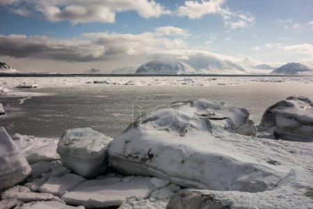 Photo pour Photo de rivage gelé enneigé avec glace et pierres - image libre de droit