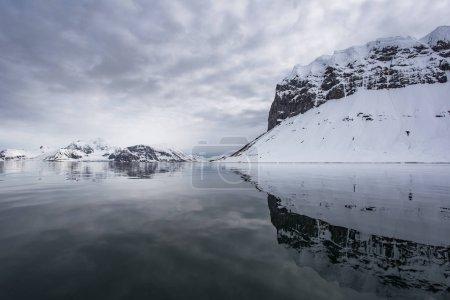 Photo pour Vue sur la côte rocheuse enneigée d'Arctica depuis l'eau - image libre de droit
