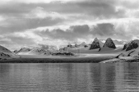 Photo pour Vue sur les rochers enneigés arctiques et les glaciers depuis l'eau - image libre de droit