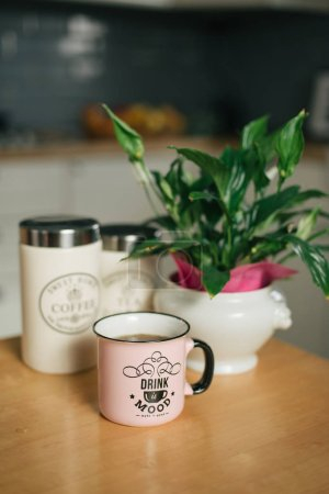 Photo for Cup of hot coffee and flower pot on wooden kitchen table - Royalty Free Image